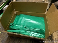 open box of green plastic trash liners